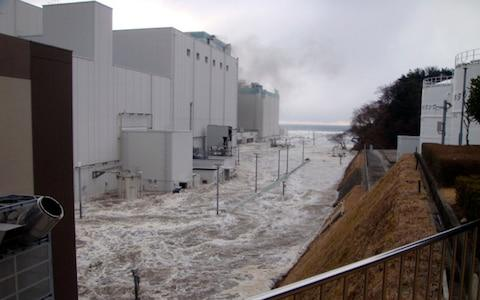 In this March 11, 2011 photo released Monday, April 11, 2011 by Tokyo Electric Power Co.,(TEPCO), the access road at the compound of the Fukushima Dai-ichi nuclear power plant is flooded as tsunami hit the facilit - Credit: AP