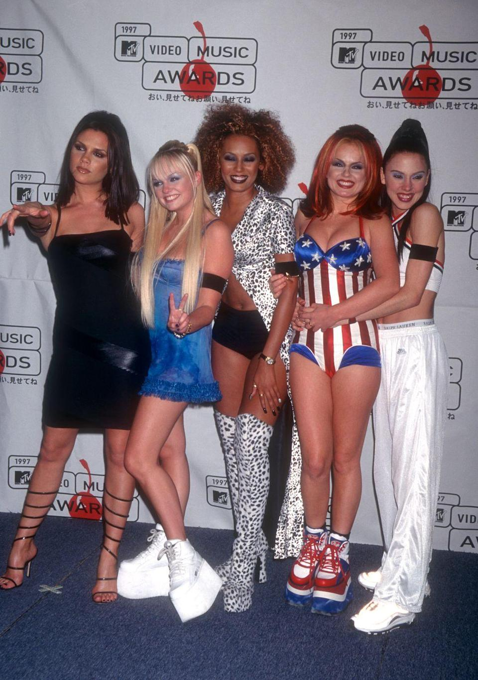 <p>Each of the five Spice Girls wore something unique to the 1997 VMAs: Posh wore a black bodycon dress with spiral heels, Baby wore a blue minidress with platform sneakers, Scary wore short shorts with dalmatian-print thigh-high boots and a matching duster blouse, Ginger wore an American-flag bodysuit with coordinating platforms, and Sporty wore a high-necked crop top with white track pants and tennis shoes.</p>