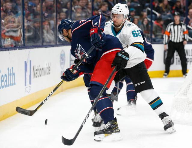 Columbus Blue Jackets' Seth Jones, left, tries to clear the puck as San Jose Sharks' Kevin Labanc defends during the first period of an NHL hockey game Saturday, Jan. 4, 2020, in Columbus, Ohio. (AP Photo/Jay LaPrete)
