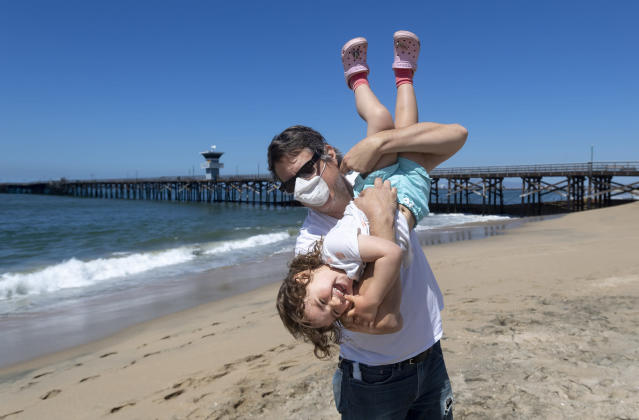 A masked man plays with his daughter on Seal Beach, California. (Getty Images)