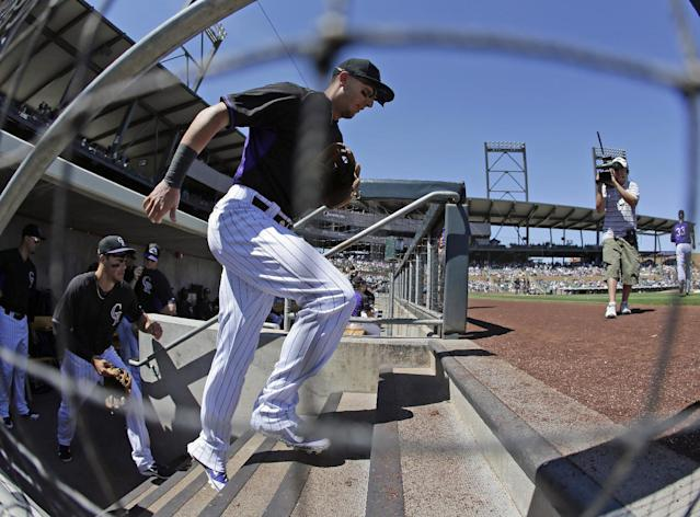 In this photo taken with a fisheye lens, Colorado Rockies shortstop Troy Tulowitzki runs onto the field for a spring exhibition baseball game against the Seattle Mariners Saturday, March 29, 2014, in Scottsdale, Ariz. (AP Photo/Darron Cummings)