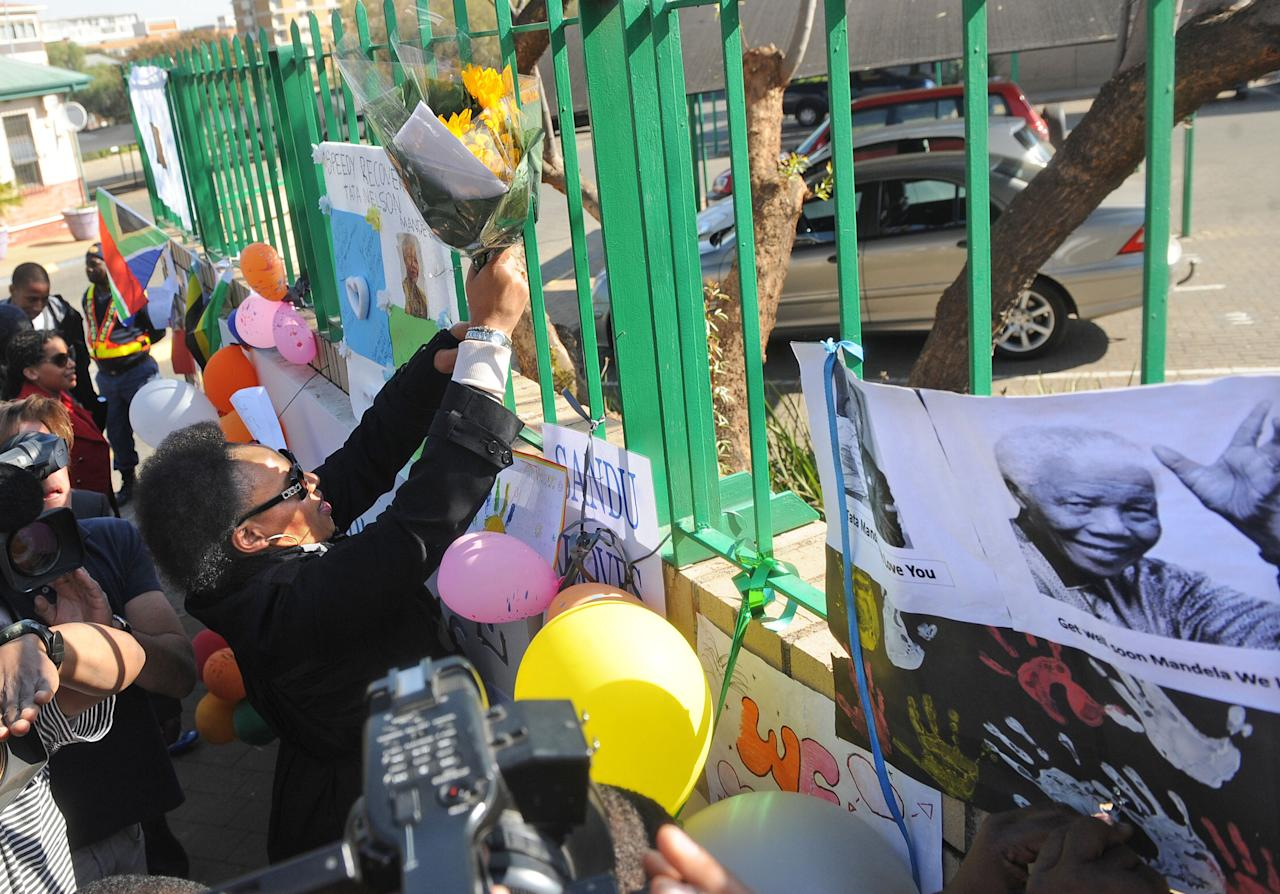 Daughter Zenani Dlamini-Mandela, left, removes flowers, placed by wellwishers on a fence at the Mediclinic Heart Hospital for her father former South African President Nelson Mandela, portrait right, who is being treated in hospital in Pretoria, South Africa Monday, June 17, 2013. In tweets, songs, telephone calls, cards and more, messages of love have come from across South Africa and the world for 94-year-old Nelson Mandela, giving the family comfort and hope as he remains hospitalized in a serious condition with a lung infection, his wife Graca Machel said in a statement Monday. (AP Photo/Antoine de Ras-Independent Newspapers South Africa Ltd) SOUTH AFRICA OUT