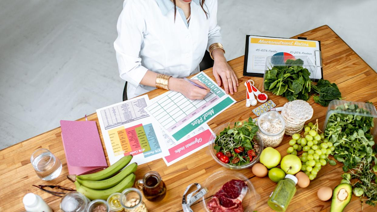 Dietitian writing a diet plan, view from above on the table with different healthy products and drawings on the topic of healthy eating.