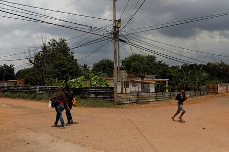 People walk by a dirt road at Rafael Urdaneta slum in Maracaibo, Venezuela July 25, 2018. Picture taken July 25, 2018. REUTERS/Marco Bello