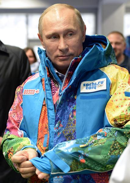 Russian President Vladimir Putin tries on a jacket during a visit the training center for volunteers Winter Olympics at the Black Sea resort of Sochi, southern Russia, Saturday, Jan. 4, 2014. Russian President Vladimir Putin has rescinded a blanket ban on demonstrations in Sochi in and around the Winter Olympics and Paralympics. (AP Photo/RIA-Novosti, Alexei Nikolsky, Presidential Press Service)