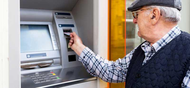 Elderly man uses an ATM.