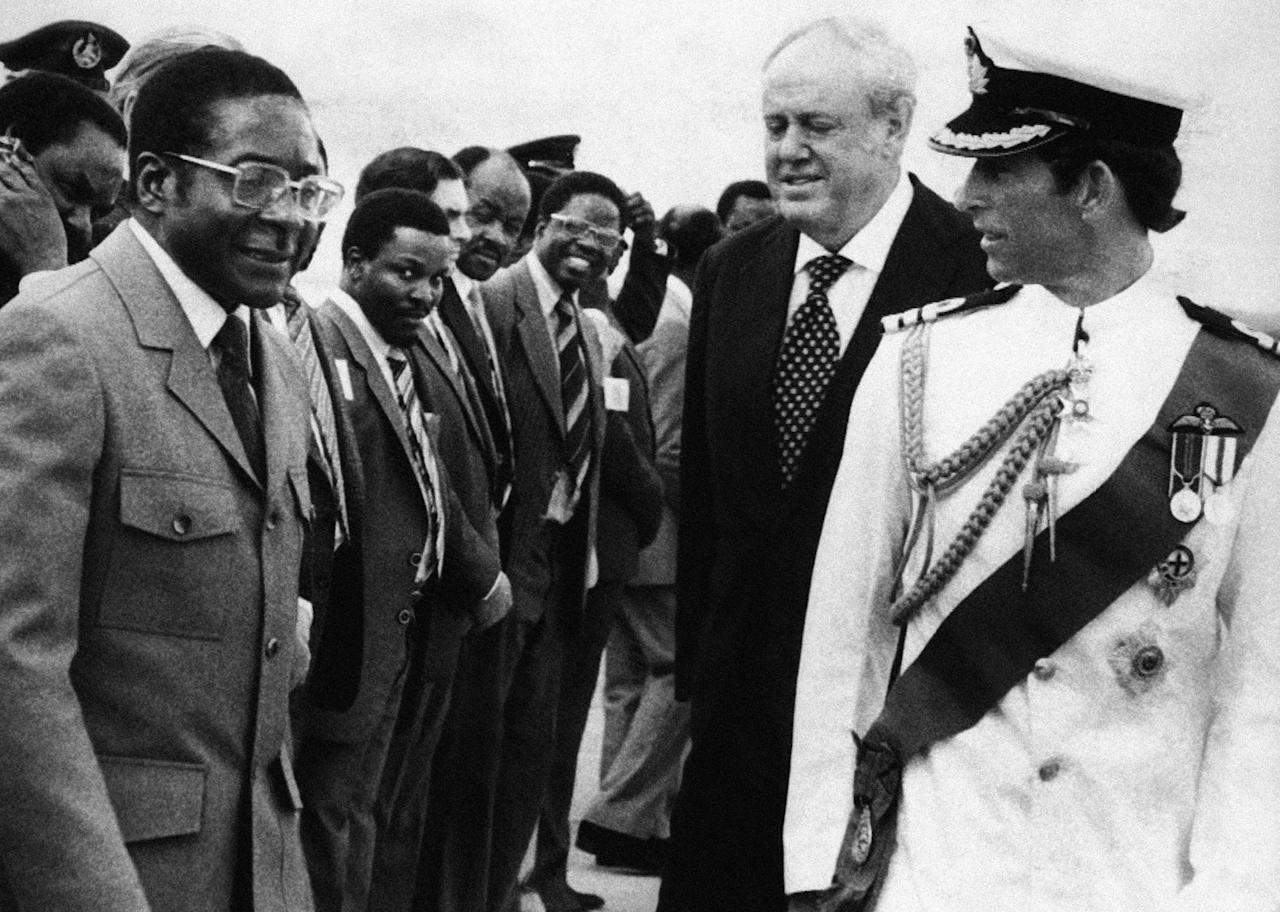 <p>Britain's Prince Charles shares a word with Zimbabwean Prime Minister Robert Mugabe, while British Governor Christopher Soames and the Rhodesian cabinet look on, in Salisbury (now Harare), Rhodesia (now Zimbabwe), on April 16, 1980. (Photo: AP) </p>