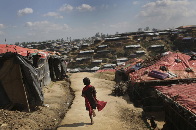 """In this Sunday, Nov. 19, 2017, photo, a Rohingya Muslim child runs on a dirt track between tents at Kutupalong refugee camp in Bangladesh. More than 620,000 Rohingya have fled Rakhine for neighbouring Bangladesh since late August 2017, when the military launched what it called """"clearance operations"""" in response to insurgent attacks. (AP Photo/Wong Maye-E)"""
