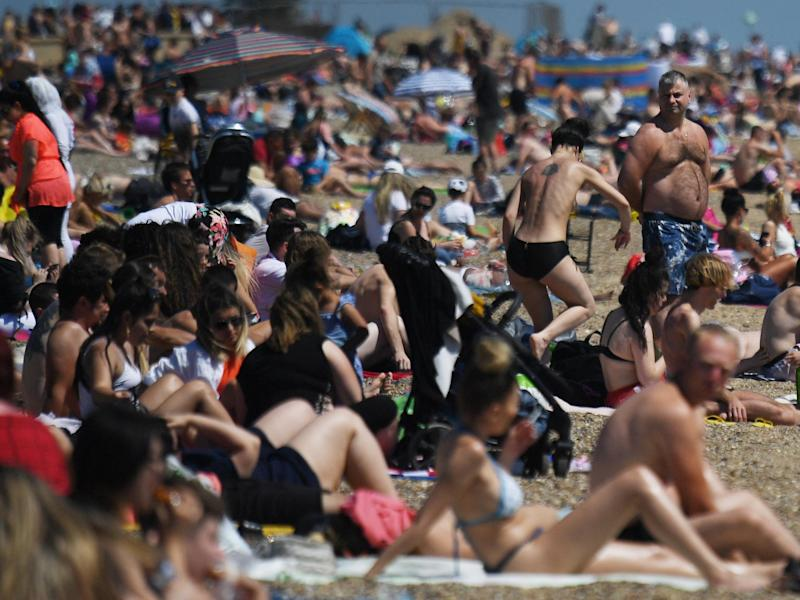 People enjoy the sunshine on the beach at Southend-On-Sea in Essex on Saturday: EPA/NEIL HALL