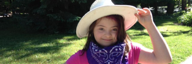 Summer camps for kids with disabilities. Little girl with Down syndrome holding on to cowboy hat.