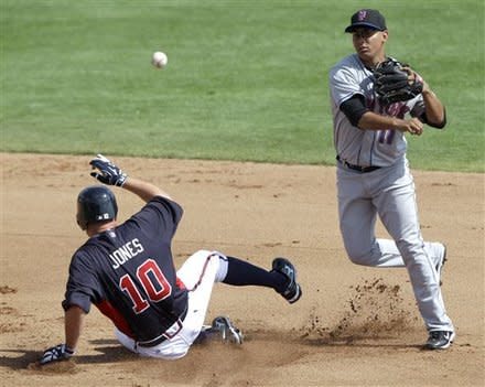 Chipper Jones slides into second while trying to break up a double play during the fourth inning against the Mets