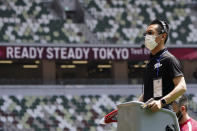 An official wears a face mask as he uses a starter pistol to signal the start a women's 100 meter heat at an athletics test event for the Tokyo 2020 Olympics Games at National Stadium in Tokyo, Sunday, May 9, 2021. Japan, seriously behind in coronavirus vaccination efforts, is scrambling to boost daily shots as the start of the Olympics in July closes in. (AP Photo/Shuji Kajiyama)