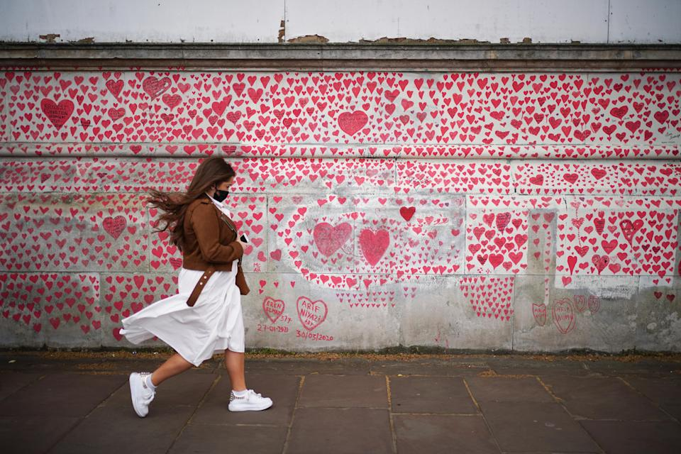 A woman walks past the National Covid Memorial Wall on the Embankment in London, following the further easing of lockdown restrictions in England. Picture date: Monday May 3, 2021.