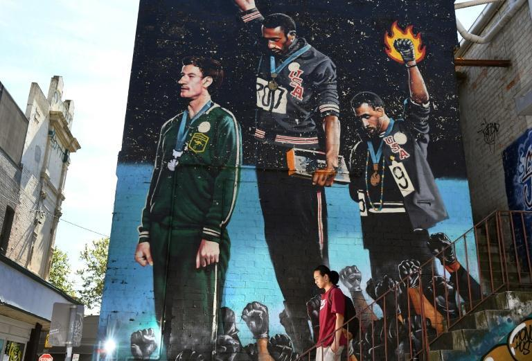 A mural depicting the iconic 1968 protest of US sprinters Tommie Smith and John Carlos adorns a wall in Melbourne