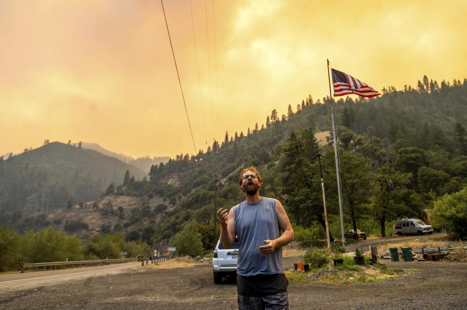Benjamin Bell watches as the Dixie Fire burns along Highway 70 in Plumas National Forest, Calif., on Friday, July 16, 2021. (AP Photo/Noah Berger)