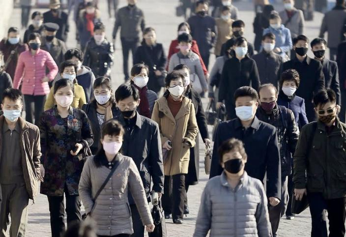 FILE PHOTO: People wearing protective face masks commute amid concerns over the new coronavirus disease in Pyongyang, North Korea