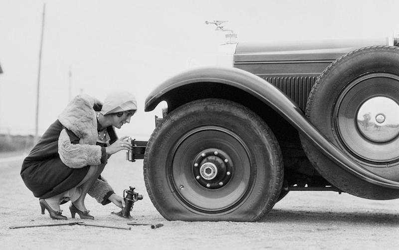 1930s woman changing flat tyre on car - Credit: H.Armstrong Roberts/Getty Images