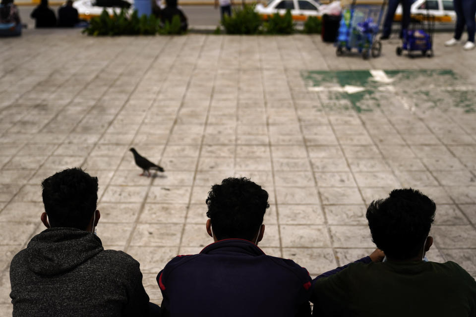 """FILE - In this May 13, 2021 file photo, Honduran migrants sit in a plaza at the border after being returned from the U.S. to Mexico, in Reynosa, Mexico. More than 70 organizations from Mexico and the United States signed an open letter on Tuesday, Aug. 24, 2021, in which they asked the government of Andres Manuel Lopez Obrador to oppose the reinstatement of the program for the return of asylum seekers implemented by former President Donald Trump and popularly known as """"Stay in Mexico"""". (AP Photo/Gregory Bull, File)"""