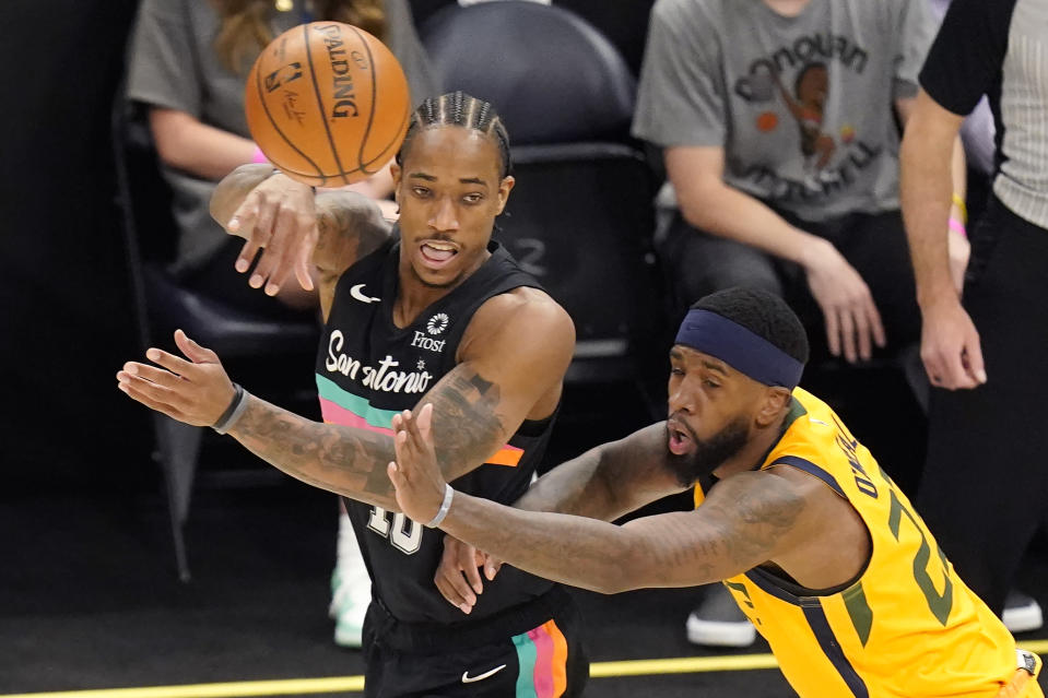San Antonio Spurs forward DeMar DeRozan, left, passes the ball as Utah Jazz forward Royce O'Neale, right, defends in the first half during an NBA basketball game Monday, May 3, 2021, in Salt Lake City. (AP Photo/Rick Bowmer)