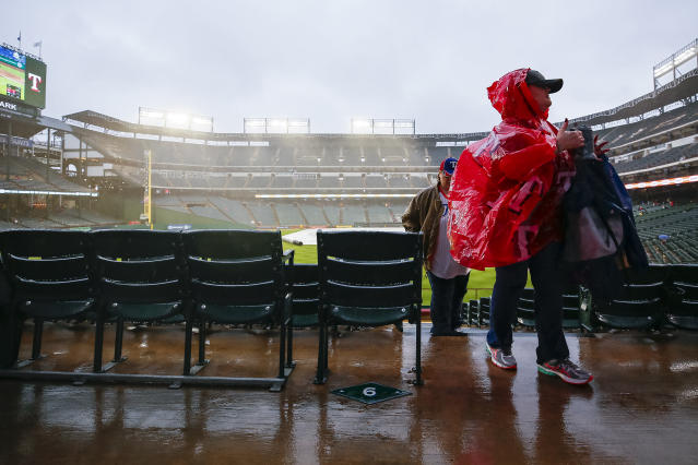 Baseball fans wait out a rain delay before a baseball game between the Oakland Athletics and the Texas Rangers, Saturday, April 13, 2019, in Arlington, Texas. The Rangers delayed the start time of Saturday's game due to inclement weather. (AP Photo/Sam Hodde)