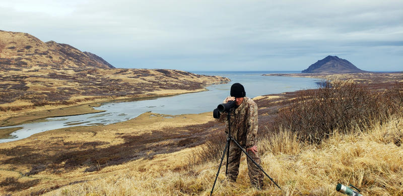 This May, 2019 photo provided by Aleksandr Neverov shows Viacheslav Akimenko using a spotting scope at Sturgeon Lagoon near Kodiak, Alaska, shortly before he died. Akimenko left the men's hunting camp, and Neverov found his friend's body six days later, about a mile from camp with no apparent signs the man was mauled by a bear or harmed himself. (Aleksandr Neverov via AP)