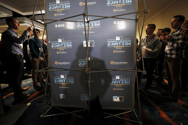 San Francisco Giants manager Gabe Kapler, center, casts a shadow as he speaks with reporters during the Major League Baseball winter meetings, Tuesday, Dec. 10, 2019, in San Diego. (AP Photo/Gregory Bull)