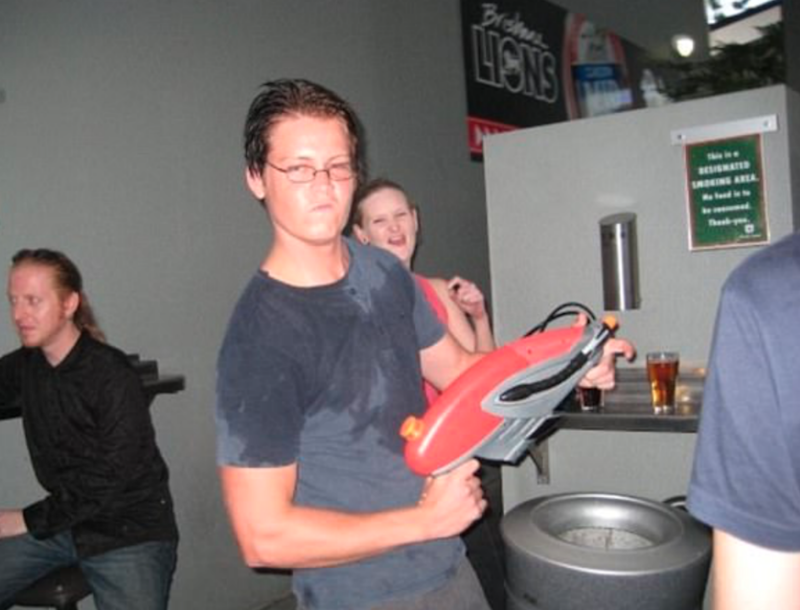The 34-year-old traded in his blonde tips for dark hair posing with a super soaker in a bar. Source: Facebook