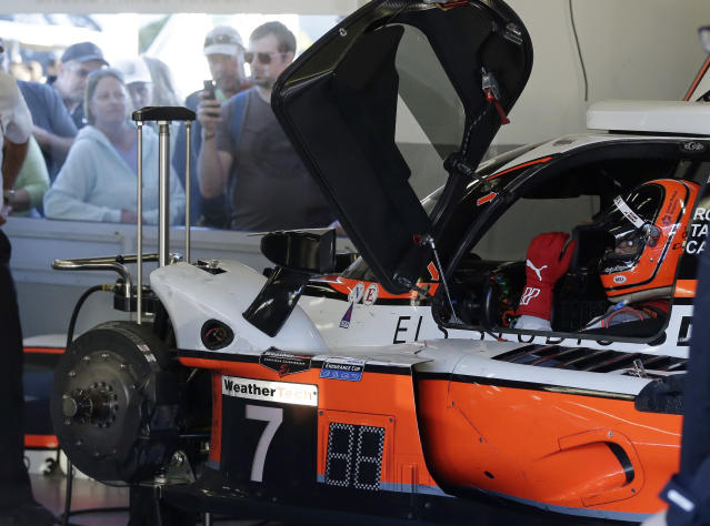 Acura Team Penske driver Helio Castroneves sits in his car while his crew makes repairs to damage from a crash during the Rolex 24 hour auto race at Daytona International Speedway, Saturday, Jan. 25, 2020, in Daytona Beach, Fla. (AP Photo/Terry Renna)