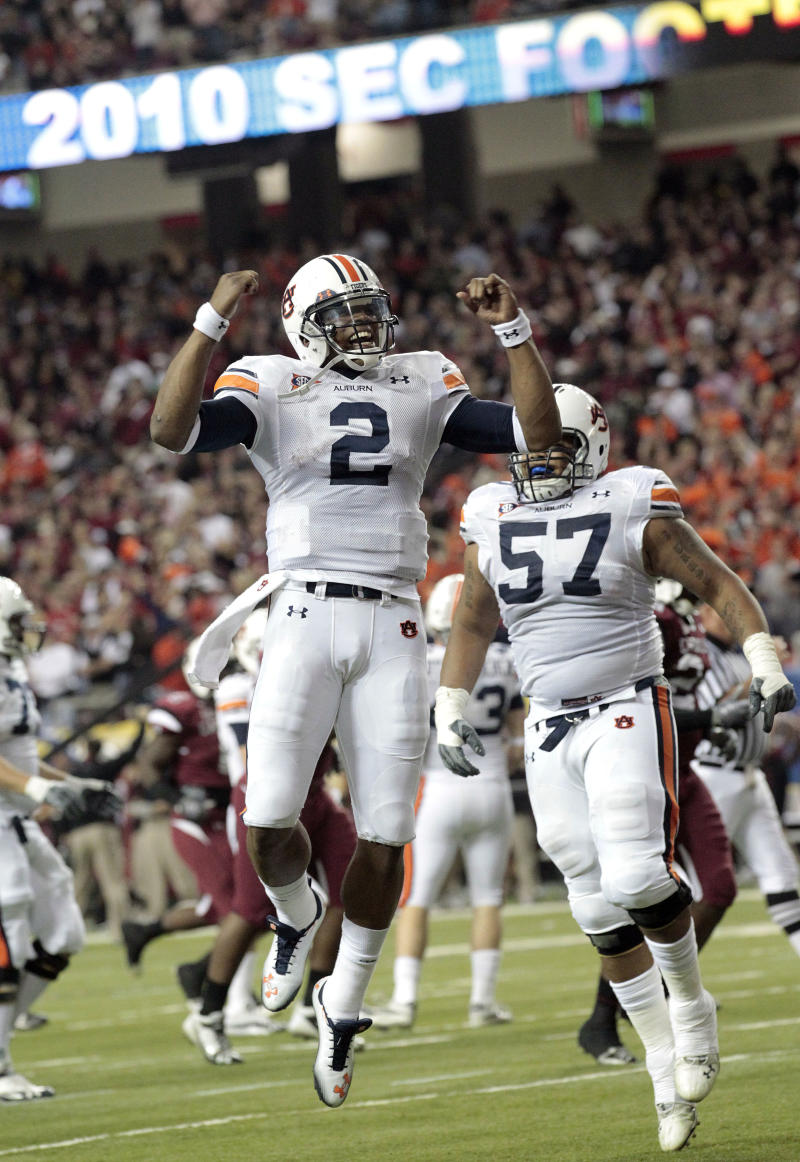 Auburn quarterback Cameron Newton, left, celebrates with teammate Byron Isom (57) after throwing a first quarter touchdown against South Carolina in the Southeastern Conference Championship NCAA college football game at the Georgia Dome in Atlanta, Saturday, Dec. 4, 2010.(AP Photo/Dave Martin)