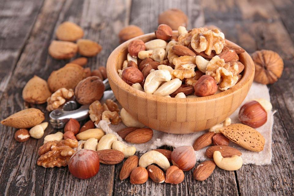 """<p>In a nutshell: USDA researchers say that eating 1.5 ounces of tree nuts daily can reduce your risk of heart disease and diabetes. Walnuts are rich in omega-3s, while hazelnuts contain arginine, an amino acid that may lower blood pressure. An ounce of almonds has as many heart-healthy polyphenols as a cup of green tea. The key is moderation since nuts are high in calories. Keep a jar of chopped nuts in your fridge, and sprinkle a tablespoon on cereal, salads, stir-fries, or yogurt. </p><p><strong>Try it: </strong><a href=""""https://www.prevention.com/food-nutrition/recipes/a20495124/tailgate-party-nut-mix/"""" rel=""""nofollow noopener"""" target=""""_blank"""" data-ylk=""""slk:Tailgate Party Nut Mix"""" class=""""link rapid-noclick-resp"""">Tailgate Party Nut Mix</a></p>"""