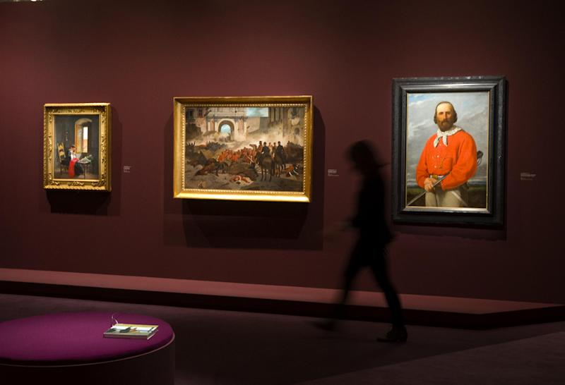 """A visitor walks past the painting ''Garibaldi in Palermo"""" (1860), center, by Giovanni Fattori,( 1825-1908) at the Orangerie Museum in Paris, Tuesday April 9, 2013. A new exhibit at Paris' Orangery museum called """"The Macchiaioli: the Italian Impressionists?"""" explores how a Florence-based art movement that predated French impressionism by a decade was already using the themes of light, the outdoors and spontaneity that's more associated with the likes of Monet or Renoir. (AP Photo/Jacques Brinon)"""