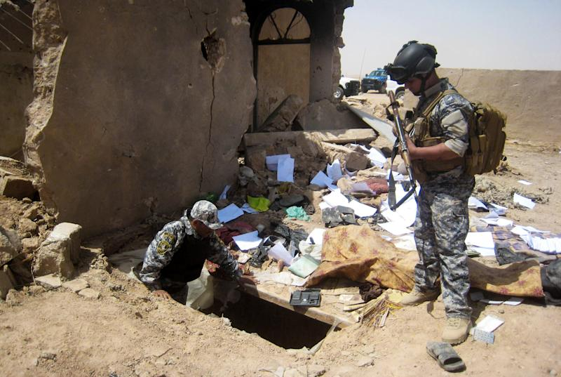 FILE - In this Tuesday, April 20, 2010 file photo, Iraqi policemen search the site of a joint U.S-Iraqi raid that killed Abu Omar al-Baghdadi and Abu Ayyub al-Masri, two top-ranking al-Qaida figures, about six miles (10 kilometers) southwest of Tikrit. The first online statement from the new leader of al-Qaida's affiliate in Iraq claims that the militant network is returning to the old strongholds from which it was driven by U.S. forces and their Sunni allies prior to the American withdrawal at the end of last year, and that it is preparing operations to free prisoners and assassinate court officials. (AP Photo, File)