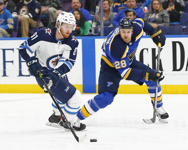 Winnipeg Jets' Kyle Connor, left, handles the puck as he is pressured by St. Louis Blues' Kyle Brodziak during the first period of an NHL hockey game Friday, Feb. 23, 2018, in St. Louis. (AP Photo/Billy Hurst)