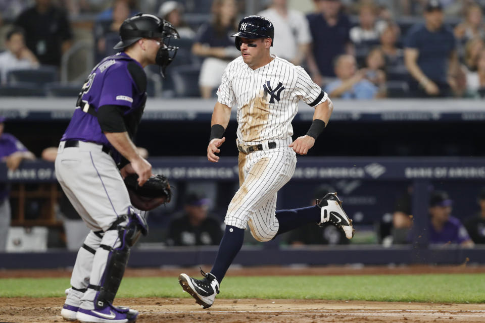 Colorado Rockies catcher Chris Iannetta, left, awaits the throw as New York Yankees' Mike Tauchman scores on DJ LeMahieu's single during the fourth inning of a baseball game Friday, July 19, 2019, in New York. (AP Photo/Kathy Willens)
