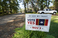 "A yard sign calling for support for the ""In God We Trust"" flag, decorates this north Jackson, Miss., neighborhood yard, Tuesday, Oct. 27, 2020. The the magnolia centered banner was chosen by the Mississippi State Flag Commission, and is on the Nov. 3 ballot. (AP Photo/Rogelio V. Solis)"