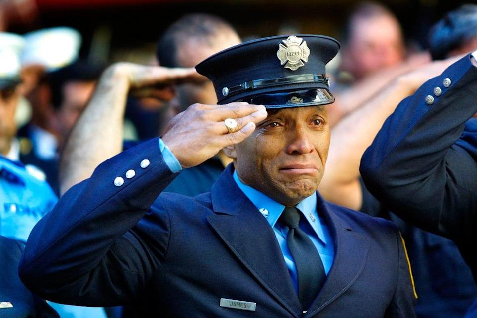 Firefighter Tony James cries while attending the funeral service for New York Fire Department Chaplain Rev Mychal Judge, in front of the St Francis of Assisi Church on 15 September, 2001. Judge died while giving the last rites to a fireman in the collapse of the World Trade Centre (Getty)