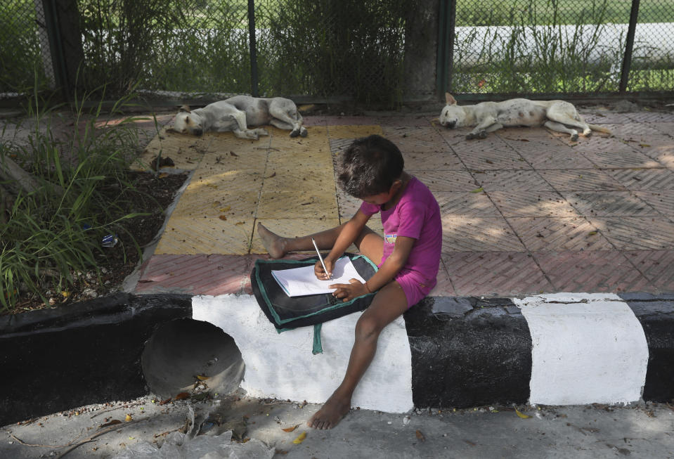 A child practices writing during a sidewalk class taught by an Indian couple, Veena Gupta and her husband Virendra Gupta, in New Delhi, India, on Sept. 3, 2020. It all began when Veena's maid complained that with schools shut, children in her impoverished community were running amok and wasting time. The street-side classes have grown as dozens of children showed keen interest. Now the Guptas, with help from their driver, teach three different groups three times a week, morning and evening. While many private schools switched to digital learning and online classes, children in most government-run schools either don't have that option or don't have the means to purchase digital learning tools like laptops and smartphones. (AP Photo/Manish Swarup)