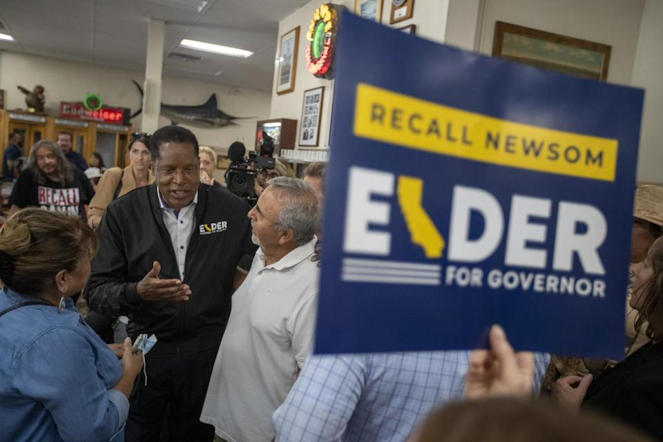 Recall candidate Larry Elder, second from left, chats with supporters during a stop at Philippe The Original deli on Monday.