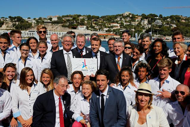 "French President Emmanuel Macron (C) poses for a family photo with International Olympic Committee (IOC) President Thomas Bach (C Right), members of the French Olympic committe, ministers and athletes as they visit the site of the future Olympic Sailing venue (Voile Olympique) at the ""Marina Olympique"" nautical base in Marseille, France, after the decision for Paris to host of the 2024 Summer Olympics Games, September 21, 2017. REUTERS/Jean-Paul Pelissier"