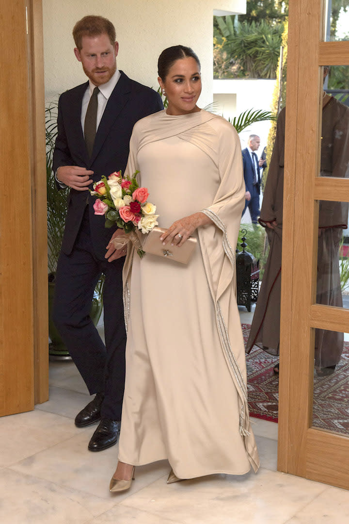 For a reception hosted by British Ambassador to Morocco, the Duchess of Sussex dressed her bump in a couture Dior dress with a matching metallic clutch and shoes. [Photo: Getty]