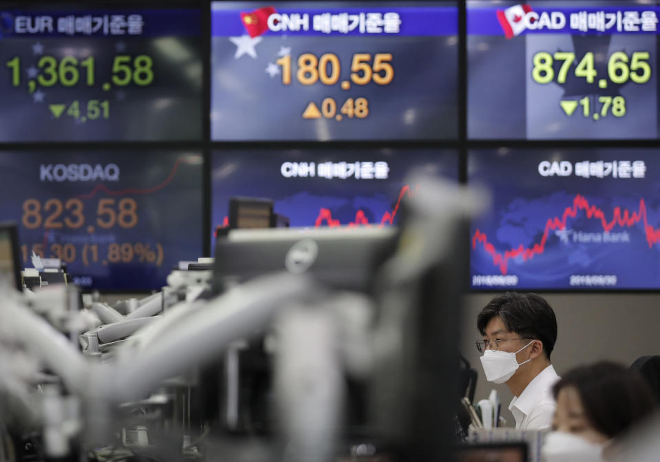Currency traders watch computer monitors near the screens showing the foreign exchange rates at the foreign exchange dealing room in Seoul, South Korea, Monday, Sept. 28, 2020. Asian shares were mostly higher in muted trading Monday, ahead of the first U.S. presidential debate and a national holiday in China later in the week. (AP Photo/Lee Jin-man)