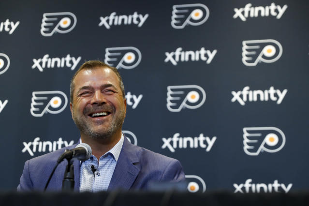In this April 18, 2019 photo, Philadelphia Flyers head coach Alain Vigneault smiles during his introductory press conference at the Flyer's practice facility in Voorhees, N.J. Vigneault, a master of quick fixes who led Vancouver and the New York Rangers to the Stanley Cup Final, was hired as the latest coach to try and win a championship for the Flyers. (AP Photo/Matt Slocum)