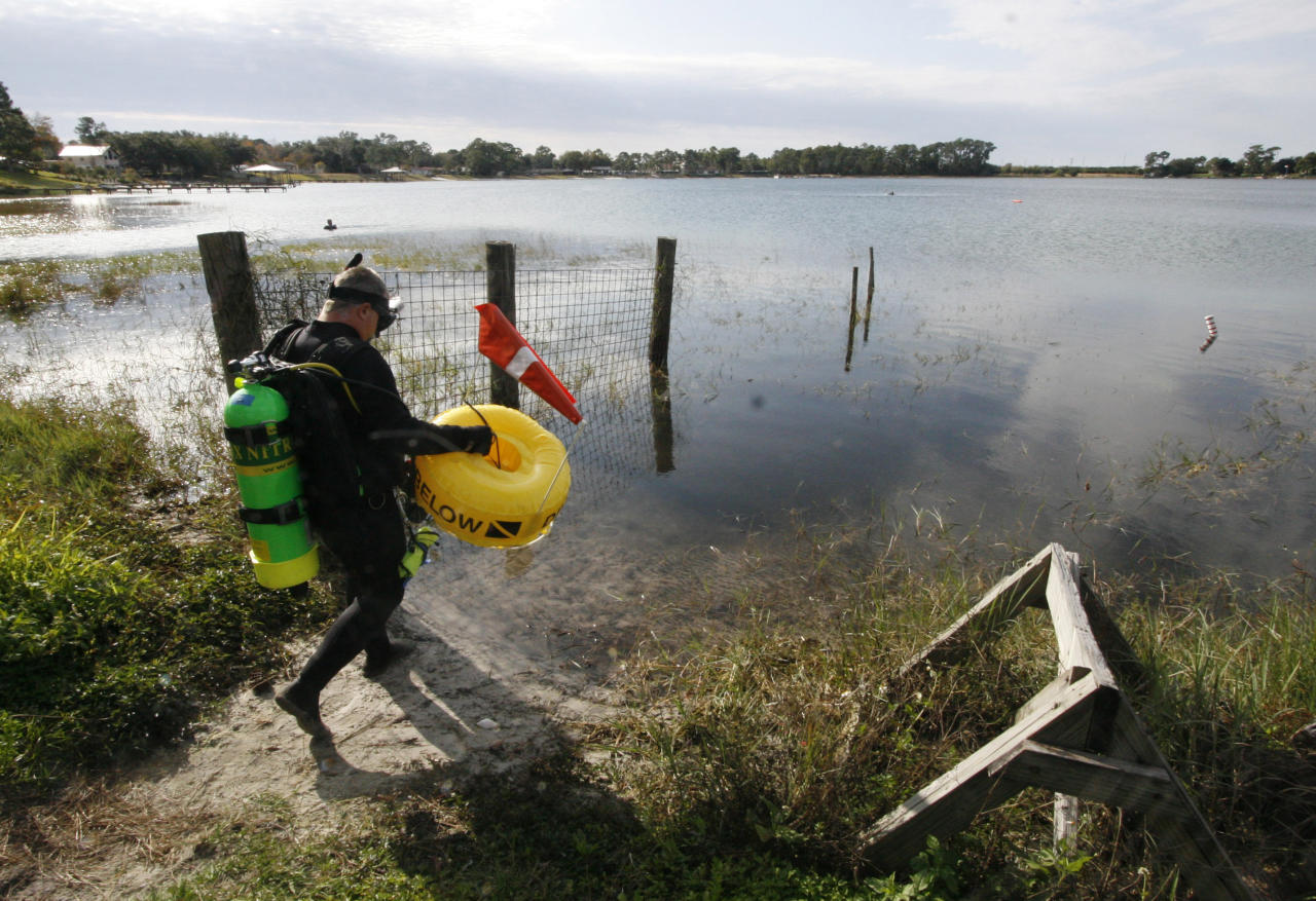 """In this Saturday, Jan. 14, 2012 photo, Kenny Jenkins carries a float with a """"Diver Down"""" flag as he prepares to place a geocache in about 33 ft. of water in Lake Denton in Avon Park Fla. Interest in geocaching has grown significantly over the years. But combining the two hobbies, geocaching and scuba diving, has only recently taken off. About 100 geocaches around the world today are only accessible with scuba gear, according to the geocaching.com database. (AP Photo/Wilfredo Lee)"""