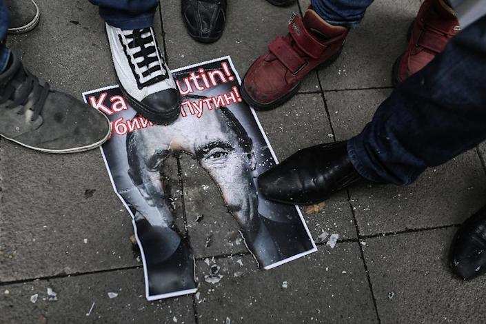 """Protesters walk over a burnt poster depicting Russian President Vladimir Putin and reading """"Putin, killer!"""" during a demonstration against Russia on November 27, 2015, in Fatih district in Istanbul (AFP Photo/Cagdas Erdogan)"""
