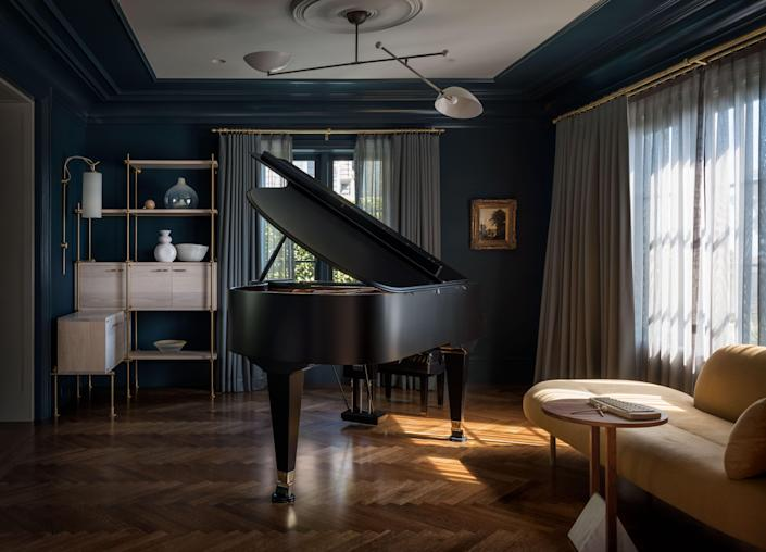 In the music room, a jet black piano is the clear center of focus.