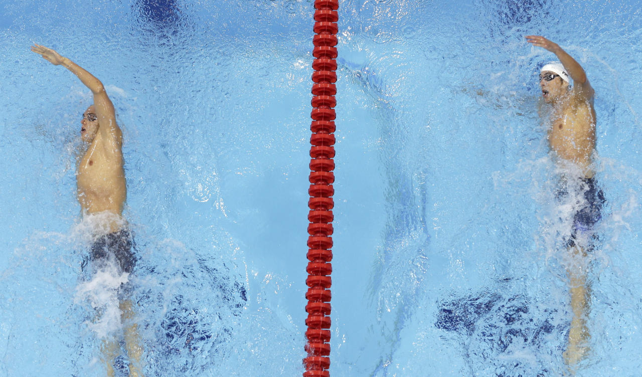 USA's Michael Phelps, right, and Hungary's Laszlo Cseh prepare to turn during a heat of the men's 400-meter individual medley at the Aquatics Centre in the Olympic Park during the 2012 Summer Olympics in London, Saturday, July 28, 2012. (AP Photo/Mark Duncan)