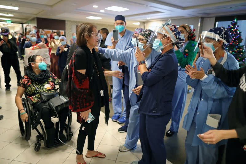 Intensive Care Unit Nurse Merlin Pambuan, is cheered by hospital staff as she walks out of the hospital where she spent 8 months with the coronavirus disease (COVID-19), at Dignity Health in Long Beach