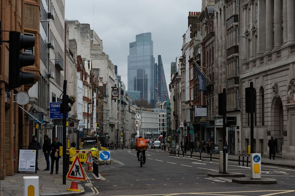 LONDON, UNITED KINGDOM - MARCH 04, 2021: A delivery rider cycles through empty street in the City of London a day after the announcement of corporation tax increase from 19% to 25% for the most profitable companies from April 2023 in Rishi Sunak's Budget, on 04 March, 2021 in London, England. The Chancellor's tax and spending plans focus on measures to support the UK's economic recovery from the slump caused by the coronavirus pandemic with furlough scheme extended until September and budget deficit expected to reach a record of £355bn this year.- PHOTOGRAPH BY Wiktor Szymanowicz / Barcroft Studios / Future Publishing (Photo credit should read Wiktor Szymanowicz/Barcroft Media via Getty Images)