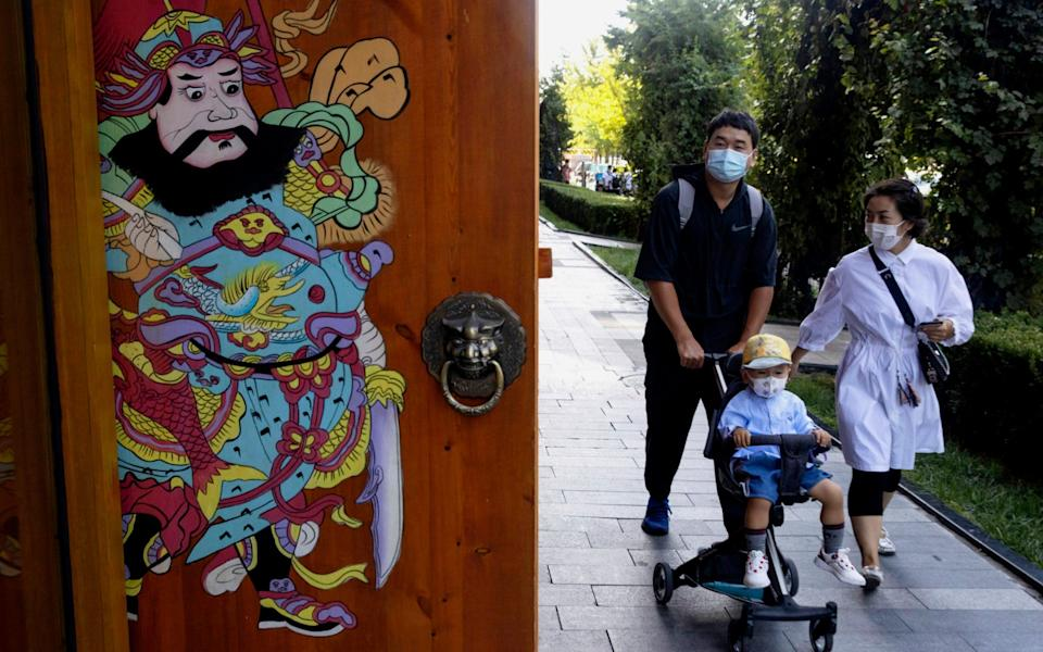 Residents wearing masks to curb the spread of the coronavirus walk on a Beijing street - AP