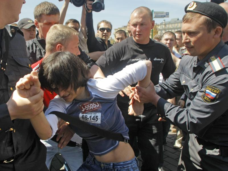 Russian police officers detain a gay activist during an attempt to hold a gay pride parade in Moscow, Russia, Saturday, May 28, 2011.  Opponents of gay rights scuffled with the demonstrators and with police in the Saturday actions. A police spokesman, Maxim Kolosvetov, told Russian news agencies that 18 gay activists and 14 opponents were arrested. Moscow authorities routinely ban gay rights demonstrations. Although homosexuality was decriminalized in post-Soviet Russia, anti-gay sentiment is high and authorities justify the bans on the grounds of trying to prevent fights.  (AP Photo/Mikhail Metzel)
